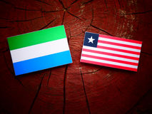 Sierra Leone flag with Liberian flag on a tree stump isolated. Sierra Leone flag with Liberian flag on a tree stump Stock Photo