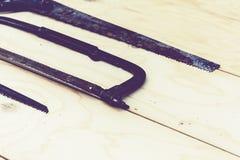 Sierras de mano usadas bien en el fondo de los tableros de madera, concepto retro fotos de archivo libres de regalías