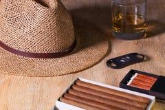 Siesta - сигары, соломенная шляпа и шотландский виски на деревянном столе Стоковое фото RF