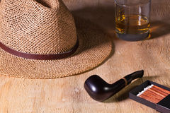 Siesta - труба, соломенная шляпа и шотландский виски на деревянном столе Стоковая Фотография RF