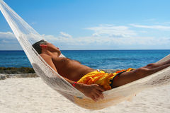 Siesta. Goodlooking man, asleep in a hammock on a tropical beach Royalty Free Stock Photos