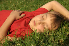 Siesta. A child takes an afternoon nap in a park Stock Images