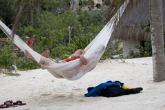 Siesta. A couple lazily laying in the hammock at the beach Royalty Free Stock Image