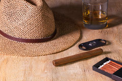 Siesta - cigar, straw hat and Scotch whiskey on a wooden desk Royalty Free Stock Images
