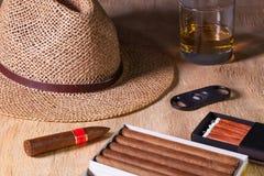 Siesta - cigars, straw hat and Scotch whiskey on a wooden desk. Siesta - cigars, straw hat and Scotch whiskey on a wooden table Royalty Free Stock Image