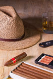 Siesta - cigars, straw hat and Scotch whiskey on a wooden desk Royalty Free Stock Images