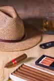 Siesta - cigars, straw hat and Scotch whiskey on a wooden desk. Siesta - cigars, straw hat and Scotch whiskey on a wooden table Royalty Free Stock Images