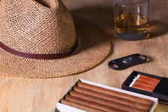Siesta - cigars, straw hat and Scotch whiskey on a wooden desk. Siesta - cigars, straw hat and Scotch whiskey on a wooden table Royalty Free Stock Photo