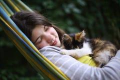 Siesta de la muchacha del adolescente en hamaca con el pequeño gatito Fotos de archivo