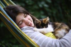 Siesta de la muchacha del adolescente en hamaca con el pequeño gatito Imagen de archivo