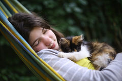 Siesta de la muchacha del adolescente en hamaca con el pequeño gatito Foto de archivo libre de regalías