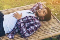 Siesta de la toma del hombre joven en la cama o el asiento de bambú Fotografía de archivo libre de regalías