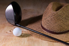 Siesta - straw hat and golf driver on a wooden desk Stock Photo