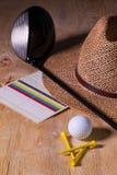 Siesta - Strohhut und Golffahrer auf einem hölzernen Schreibtisch Stockbild