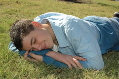 Siesta time!. Young man lays down on the ground to take a nap in the sun Stock Image