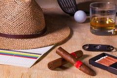 Siesta - Zigarre, Strohhut, schottischer Whisky und Golffahrer auf einem wo Stockfotos