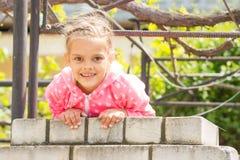 Siete años de ejecución feliz de la muchacha en una cerca del ladrillo y mirada en el marco Fotografía de archivo libre de regalías