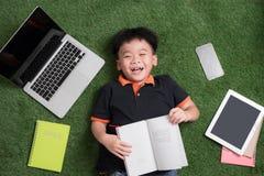 Siete años del niño que lee un libro que miente en la hierba Fotos de archivo libres de regalías