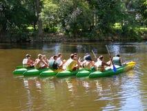 Siete canoas con la gente joven agrupada en el medio del río Imagenes de archivo