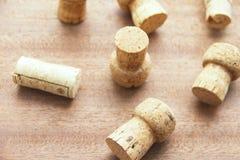 Siete casquillos de champán del corcho dispersaron aleatoriamente en un tablero de madera Foto de archivo libre de regalías