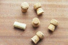 Siete casquillos de champán del corcho dispersaron aleatoriamente en un tablero de madera Fotos de archivo libres de regalías
