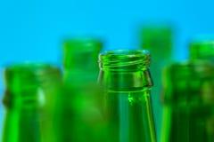 Siete cuellos verdes de la botella en fondo azul Fotografía de archivo