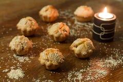Siete molletes salados acercan a la vela en la tabla de madera Foto de archivo
