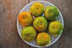 Siete naranjas en el plato Foto de archivo