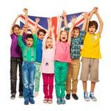 Siete niños aumentaron sus manos para arriba con la bandera inglesa Imagen de archivo libre de regalías