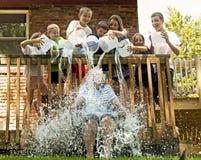 Siete niños con 7 cubos descargan el agua en mujer Imágenes de archivo libres de regalías