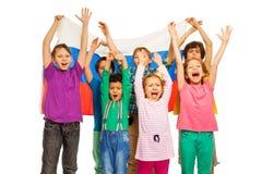 Siete niños con la bandera de la Federación Rusa detrás Imagen de archivo