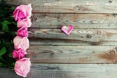Siete rosas en fondo de madera Imagenes de archivo