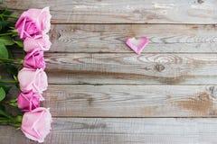 Siete rosas en fondo de madera Fotos de archivo
