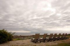 Siete sillas vacías del Recliner de la playa en una mañana nublada Fotografía de archivo