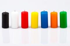Siete velas coloreadas en un fondo blanco Foto de archivo