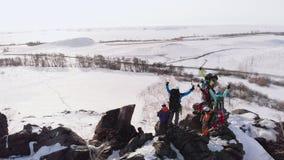 Siete viajeros en un uniforme especial y con los polos de esquí, con difícilmente trabajar su ruta a través de las nieves acumula almacen de video