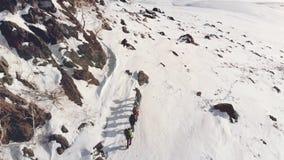 Siete viajeros están en una formación al pico de una colina nevada, de una manera ayuda a su engranaje y mochilas con metrajes