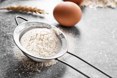 Sieve with flour on table. Sieve with flour on gray table Royalty Free Stock Image