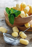 Sieve with powdered sugar and corn sticks in a bowl. Stock Photos