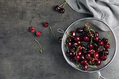 Sieve with sweet red cherries on table. Top view stock image