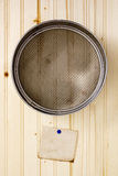 Sieve on a wooden wall Royalty Free Stock Photo