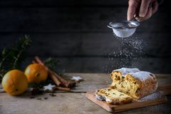 Sieving powdered sugar on a christmas cake, in germany christstollen, orange and spices blurred in the back on a rustic wooden ta. Ble, dark background with copy royalty free stock images