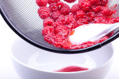 Sieving raspberries for jam Royalty Free Stock Photos