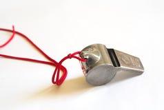 Sifflement en métal sur un cordon rouge Image libre de droits