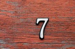 Siffra 7 på den röda sjaskiga träväggen, närbild arkivbilder