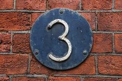 Siffra 3 på mörk metallbakgrund på väggen för röd tegelsten Royaltyfri Bild
