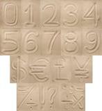 Siffror, interpunktion och valutasymboler från sanden Arkivfoton