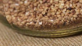 Sifting buckwheat in glass jar stock video