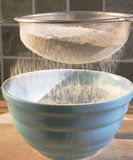 Sifting Flour. Sieving Flour into a blue bowl. Ideal shot to represent this stage in any number of recipes Royalty Free Stock Photography