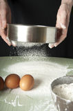 Sifting flour through a sieve Stock Images